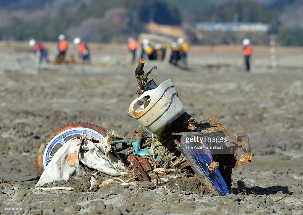 A destroyed kids bicycle is buried while police officers committed to search the missings continues to dig the 106 hectare area near Okawa Elementary School on December 11, 2012 in Ishinomaki, Miyagi, Japan. 70 out of 108 pupils of the school were killed by the earthquake triggered tsunami last year and the searching work continues on the 21 months anniversary day.