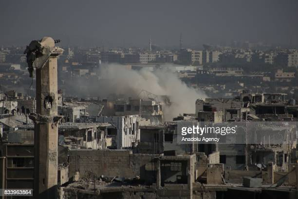 A destroyed minaret is seen as smoke rises after Assad regime forces' carried out an air strike at the Ein Terma town of Eastern Ghouta which is a...