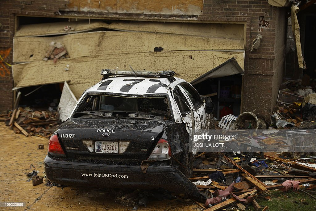 A destroyed police car is seen on May 21, 2013 in Moore, Oklahoma. Families returned to a blasted moonscape that had been an American suburb Tuesday after a monstrous tornado tore through the outskirts of Oklahoma City, killing at least 24 people. Nine children were among the dead and entire neighborhoods vanished, with often the foundations being the only thing left of what used to be houses and cars tossed like toys and heaped in big piles. AFP PHOTO/Joshua LOTT