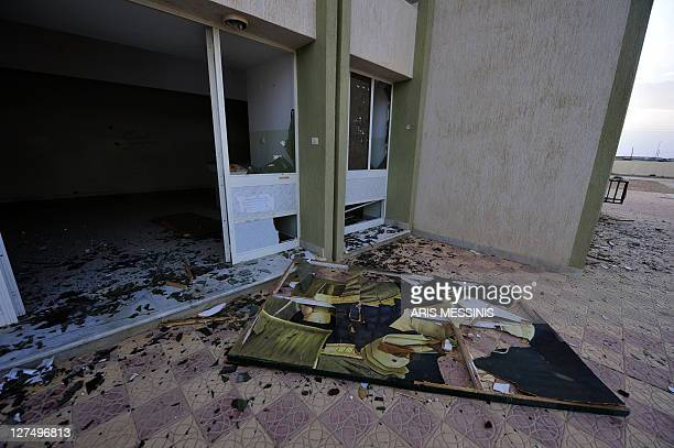 A destroyed portrait of ousted Libyan leader Moamer Kadhafi lies at the entrance to the local headquarters of Libya's former regime in Tawarga on...