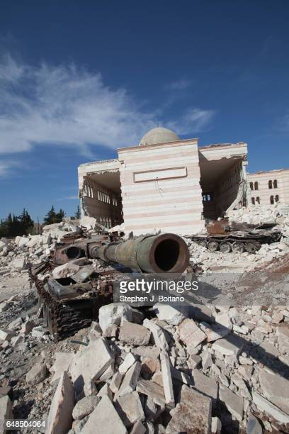A'ZAZ ALEPPO SYRIA Destroyed tanks and armored vehicles sit on display near a damaged mosque in A'zaz Syria