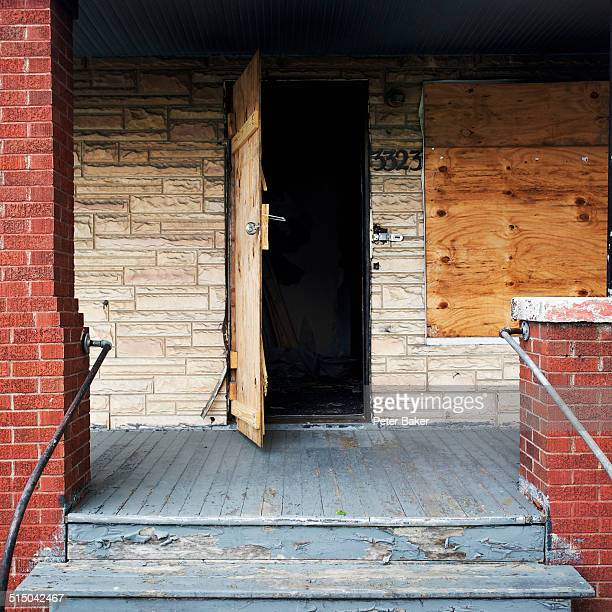 Detail an open door of a boarded up house