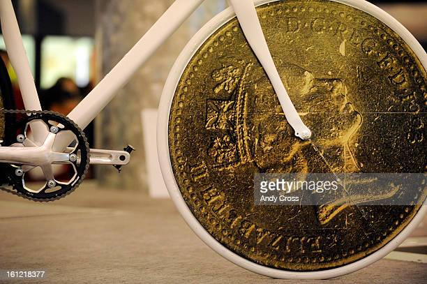 DENVER CO Detail artwork of a coin depicting Queen Elizabeth the II graces the front wheel of a bicycle that sits on top of a baggage claim carousel...