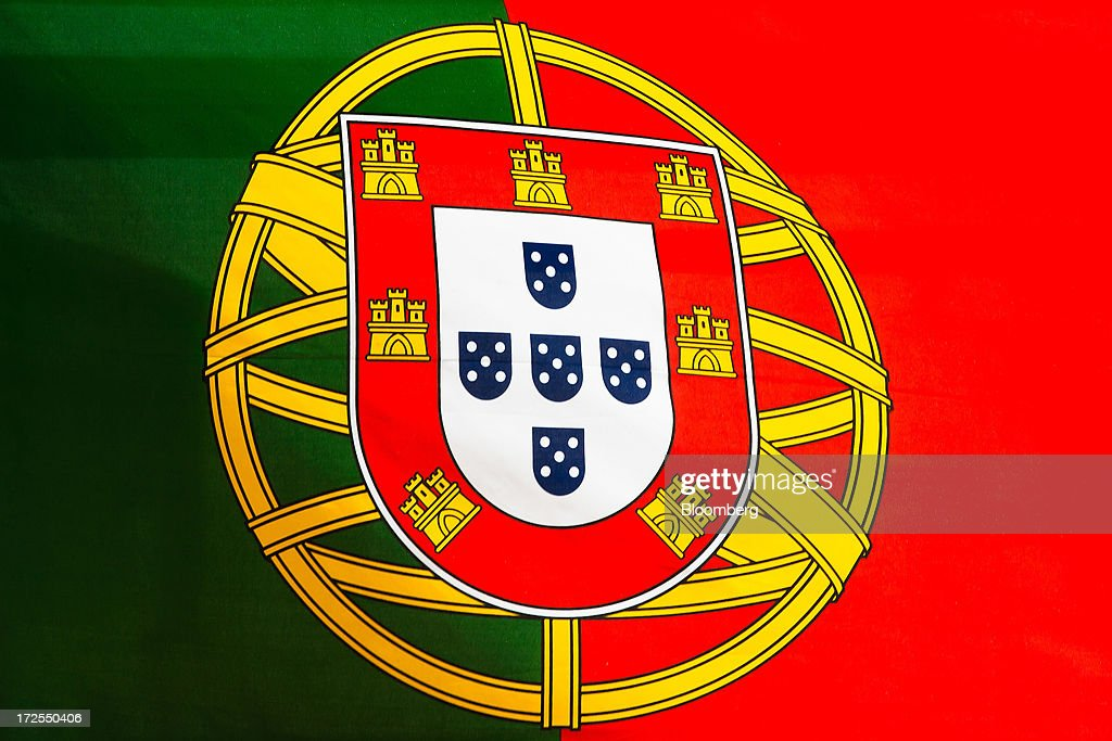 A detail from Portugal's national flag is seen hanging from a store in Lisbon, Portugal, on Wednesday, July 3, 2013. Portuguese borrowing costs topped 8 percent for the first time this year after two ministers quit, signaling the government will struggle to implement further budget cuts as its bailout program enters its final 12 months. Photographer: Mario Proenca/Bloomberg via Getty Images