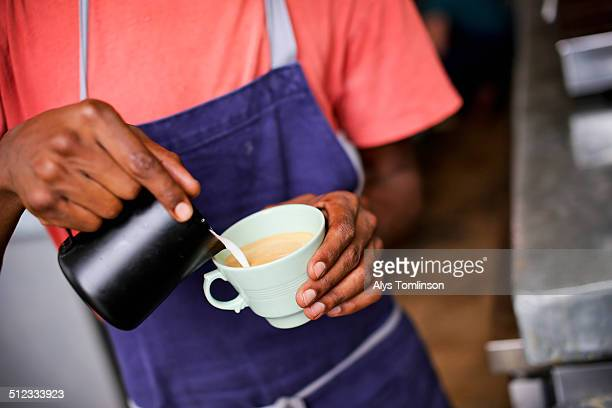 Detail of a Barista Pouring Milk into a Coffee
