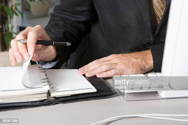 Detail of a businessman using a personal organizer at his desk