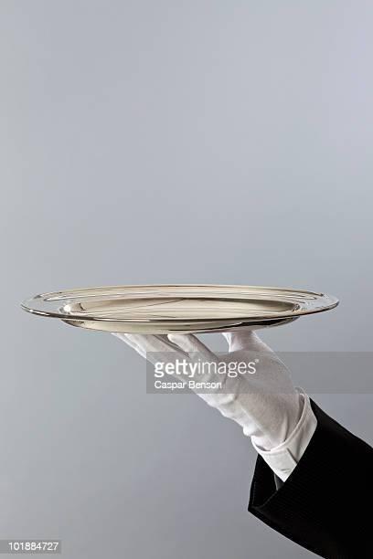 Detail of a butler holding a sliver platter