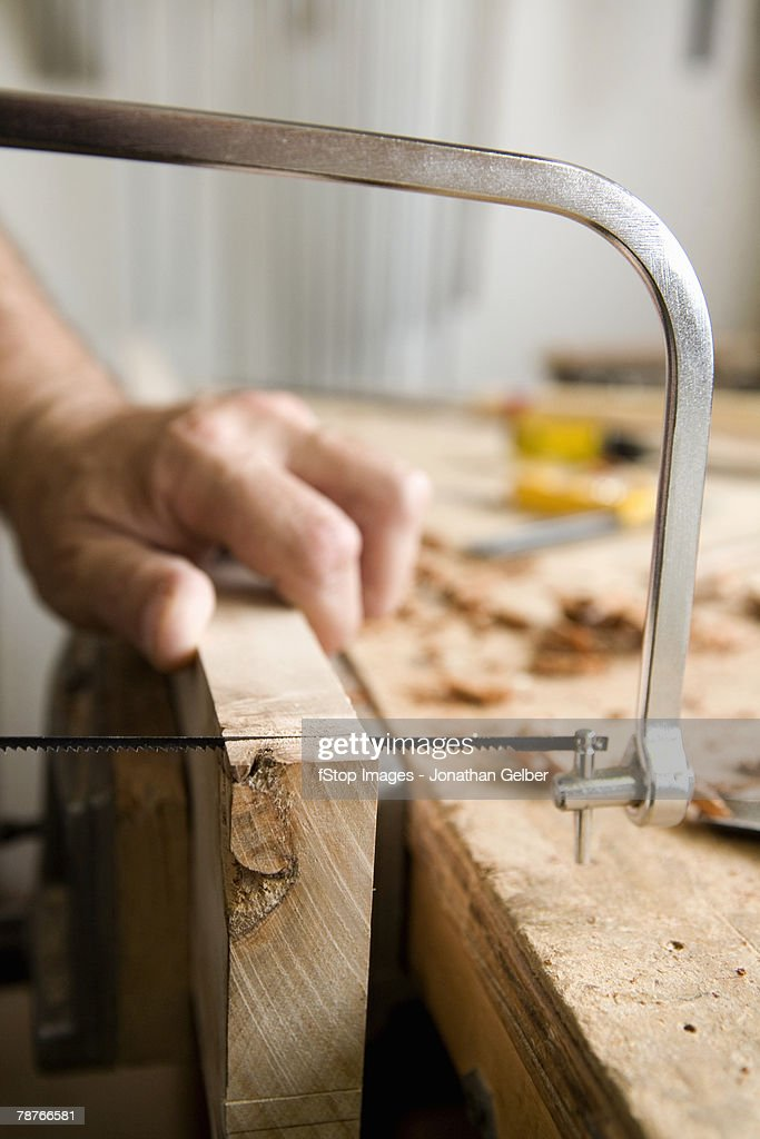 Detail of a carpenter using a hand saw