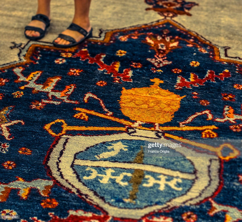 A detail of a carpet featuring a Papal symbol as a woman stands on it with her sandals at the Apostolic Palace on October 7, 2013 in Vatican City, Vatican. After the success of his Social networking accounts of Twitter and Facebook, Pope Francis joined Instagram, reporting today more than 8000 followers.
