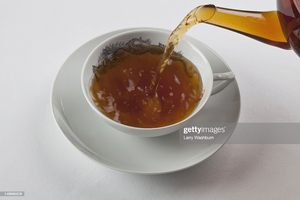 Detail of a cup of black tea being poured