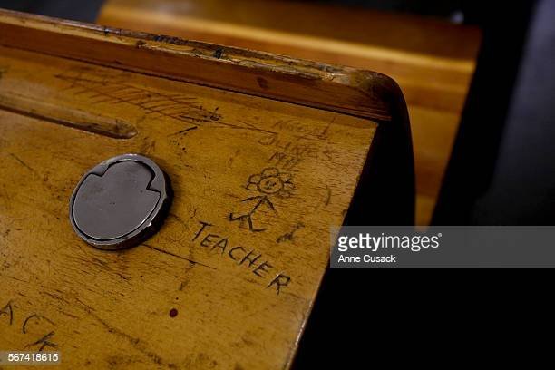 Detail of a desk from the early era LAUSD has a etching of a teacher in an exhibit of LAUSD historical items called The Art and Artifact Museum that...