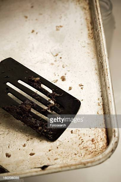 Detail of a dirty spatula on a dirty cookie sheet