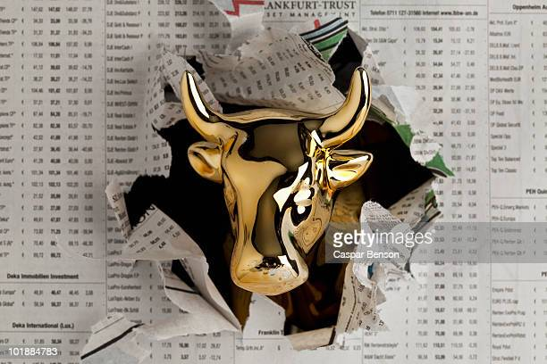 Detail of a golden bull breaking through the finance section of a newspaper