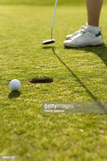 Detail of a golf ball next to a hole