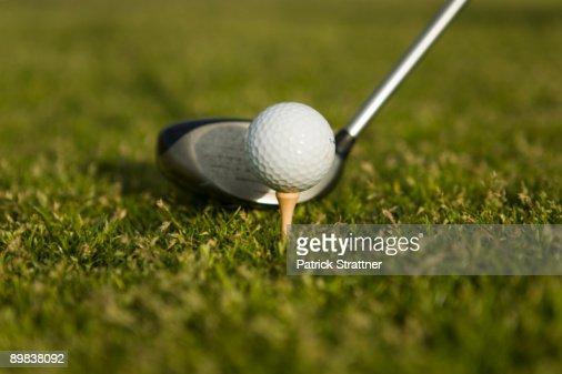 Detail of a golf club next to a golf ball on a tee