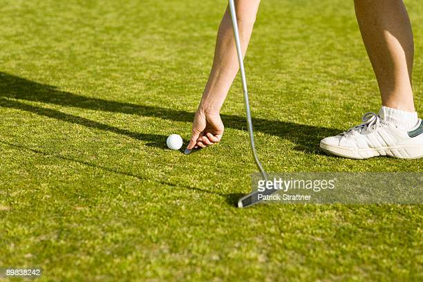 Detail of a golfer marking the ball's position with a coin