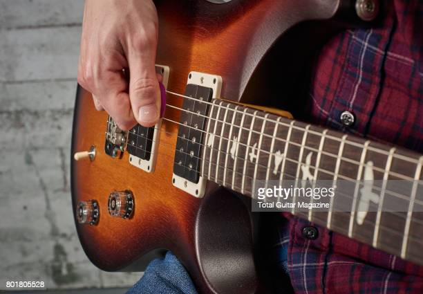 Detail of a guitarist playing a pick scrape on a PRS electric guitar taken on November 24 2016