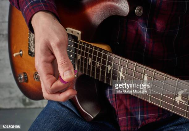 Detail of a guitarist playing a pinched harmonic on a PRS electric guitar taken on November 24 2016