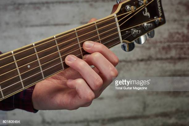 Detail of a guitarist playing an open D chord on an acoustic guitar taken on November 24 2016