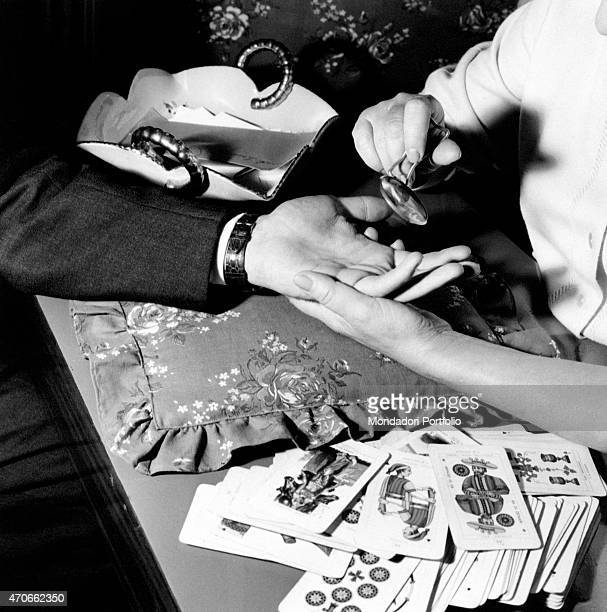 'Detail of a hand of a man posed on a pillow while a palmist reads the lines with a magnifying glass nearby in the closeup is scattered a bunch of...
