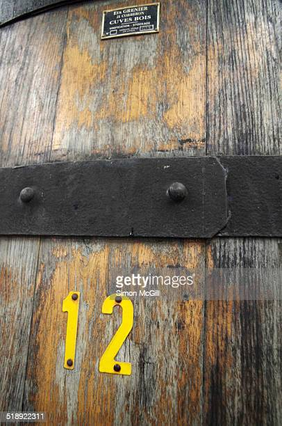 Detail of a large oak wine barrel storing maturing red wine at a winery in the Burgundy region of France