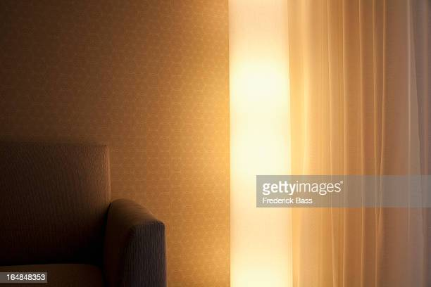 Detail of a light, sofa and curtain in a living room