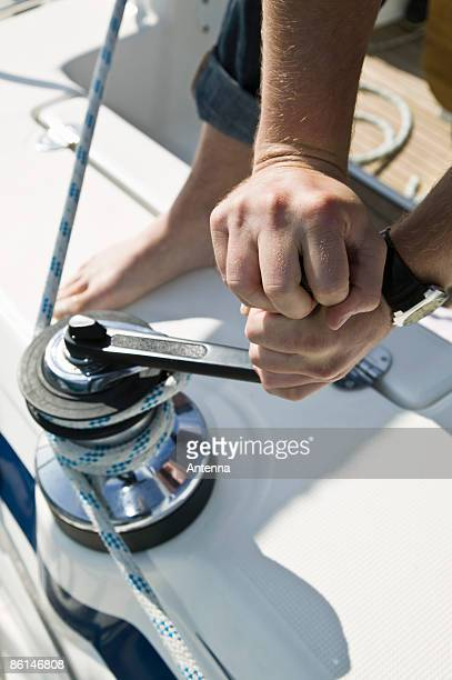 Detail of a man adjusting the rigging on a yacht
