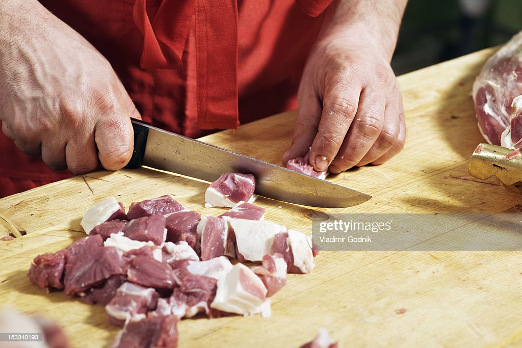Detail of a man chopping meat : Stock Photo