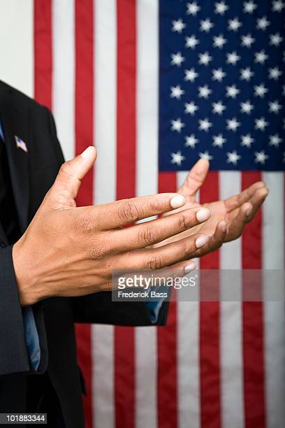 Detail of a man gesturing in front of an American flag