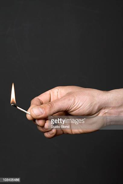 Detail of a man holding a lit match