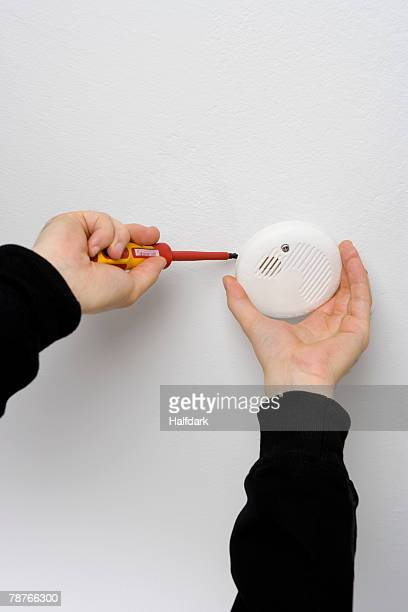 Detail of a man installing a smoke detector