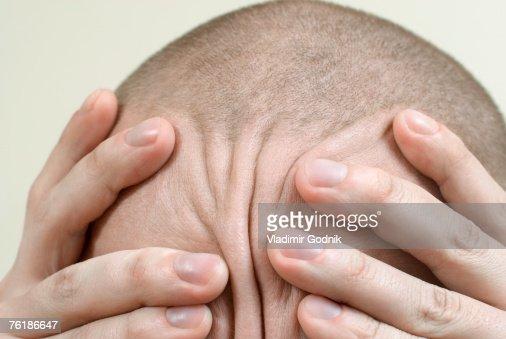 Detail of a man rubbing his head