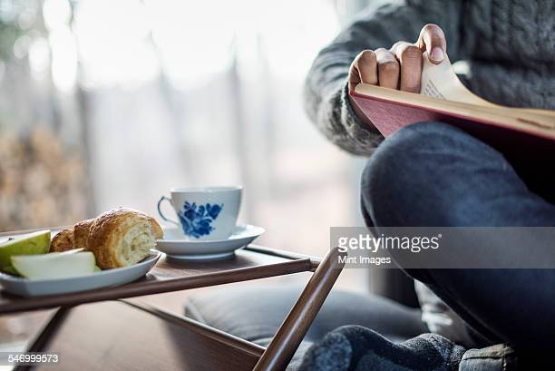 Detail of a man sitting in a chair, balancing a book on his knee, a side table with a cup and saucer and a plate with an apple and a croissant next to him.