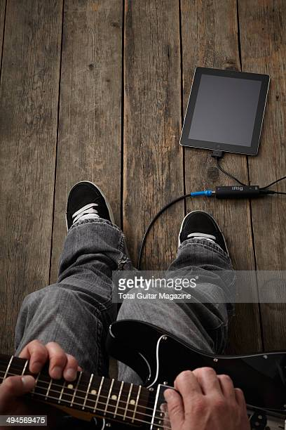 Detail of a musician with an electric guitar plugged into a Apple iPad photographed for a feature on playing music alongside iOS devices taken on...