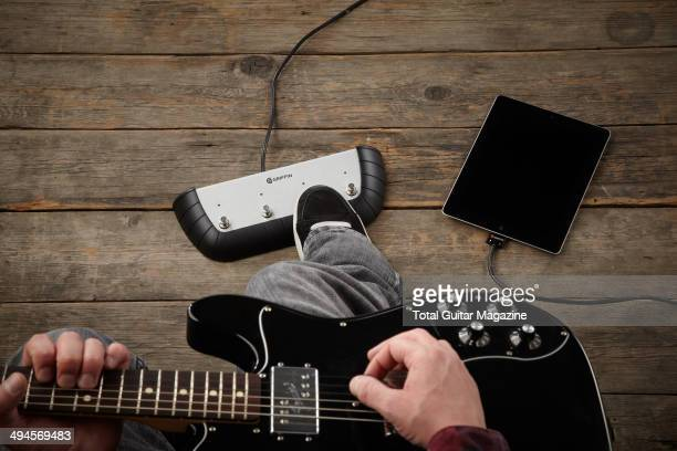 Detail of a musician with an electric guitar plugged into a Griffin StompBox and Apple iPad photographed for a feature on playing music alongside iOS...