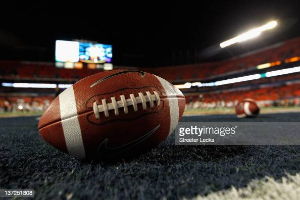 A detail of a Nike official NCAA size football as it sits in the end zone while the West Virginia Mountaineers stretchon the field prior to playing...