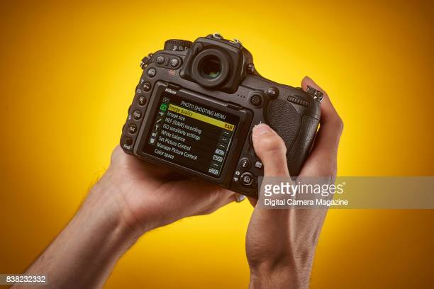 Detail of a photographer holding a Nikon D500 digital SLR camera with the LCD screen menu visible taken on August 16 2016