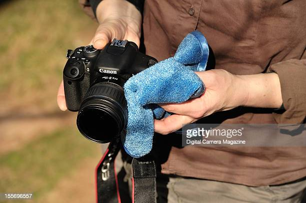 Detail of a photographer's hands wiping clean a Canon EOS 600D taken on March 27 2012