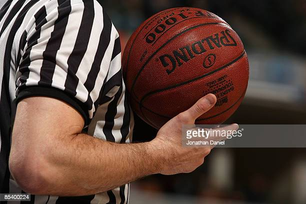 A detail of a referee holding a Spalding basketball as the Minnesota Golden Gophers play against the Northwestern Wildcats during the first round of...