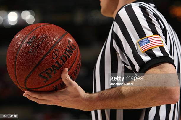 A detail of a referee holding a spalding basketball with a big ten logo on as the Wisconsin Badgers take on the Michigan State Spartans during their...
