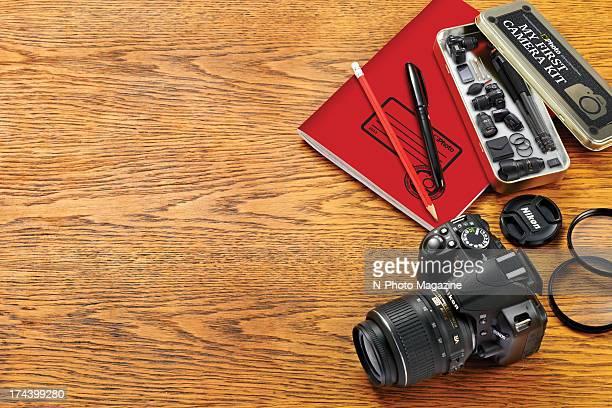Detail of a school desk and pencil case filled with miniaturised Nikon camera equipment alongside a fullsize Nikon D3100 taken on December 12 2012