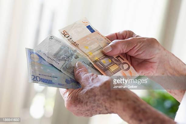 Detail of a senior woman holding European banknotes