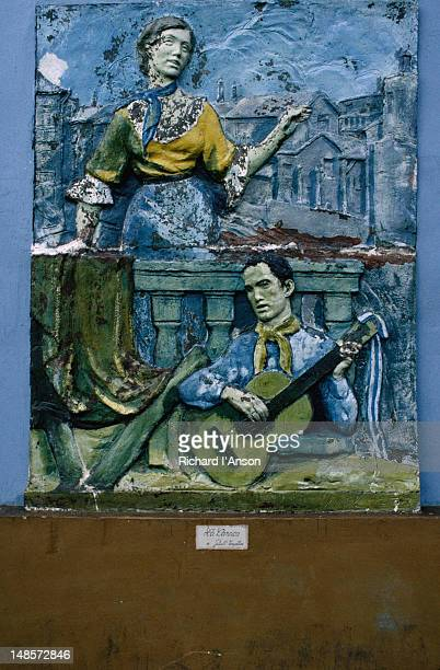 Detail of a stone relief, depicting a man and guitar serenading a woman on a balcony found in La Boca district, Buenos Aires.