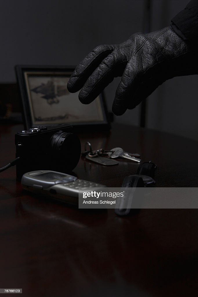 Detail of a thief reaching for a mobile phone