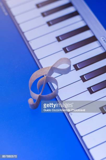 Detail of a treble clef against piano keyboard