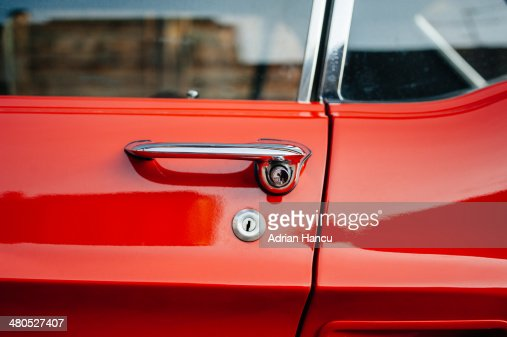 Detail of a vintage red car door handle : Bildbanksbilder