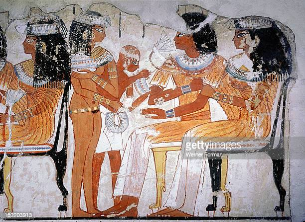 A detail of a wall painting from the tomb of Nebamun depicting two guests at a banquet They are seated on chairs and the woman wears an elaborate...