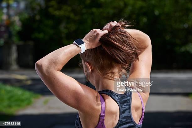 Detail of a woman in sportswear tying back her hair while modelling an Apple Watch Sport taken on May 21 2015
