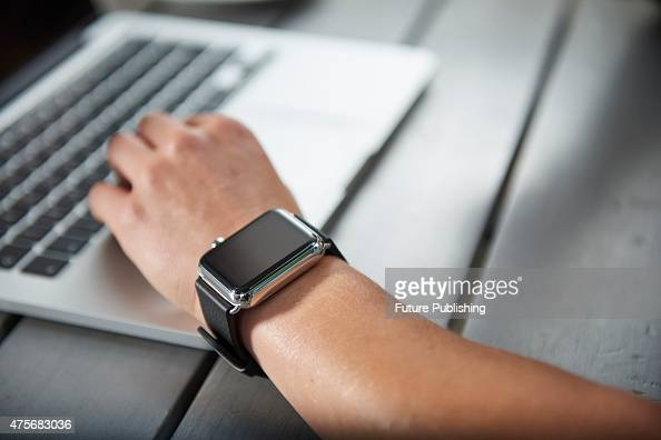 Detail of a woman wearing an Apple Watch while sitting outside a cafe with an Apple MacBook taken on May 21 2015