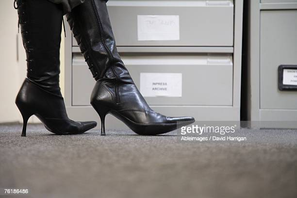 Detail of a woman wearing high heel boots standing next to filing cabinets